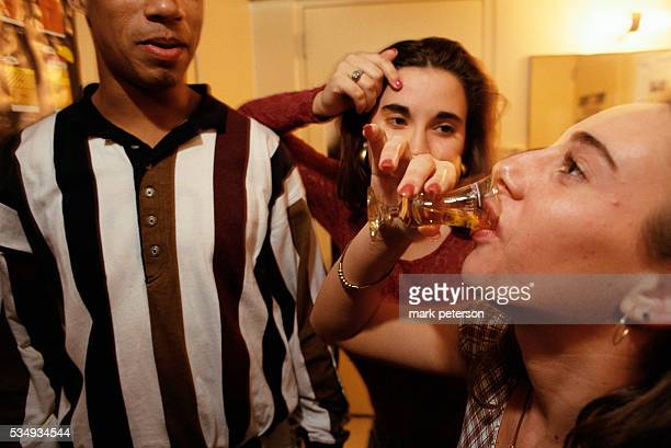 An Arizona State University student consumes a shot of alcohol during a drinking contest at Manzanita Residence Hall