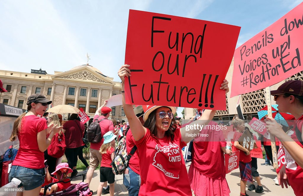 An Arizona teacher holds up a sign in front of the State Capitol during a #REDforED rally on April 26, 2018 in Phoenix, Arizona. Teachers state-wide staged a walkout strike on Thursday in support of better wages and state funding for public schools.
