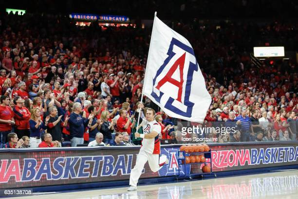An Arizona Wildcats cheerleader runs with the University of Arizona logo flag before the college basketball game between the Cal Golden Bears and the...