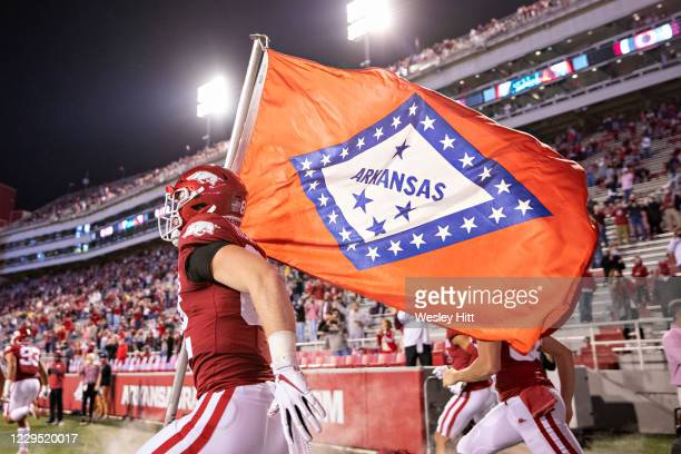An Arkansas Razorbacks player runs the Arkansas State flag onto the field before a game against the Tennessee Volunteers at Razorback Stadium on...