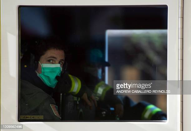 An Arlington county firefighter looks on from an engine after responding to a dispatch call in Arlington Virginia on April 9 2020 Firefighters in the...