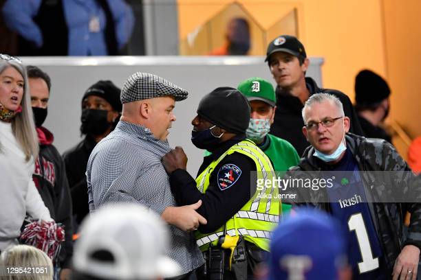 An Arlington police officer tries to control a fan during the College Football Playoff Semifinal at the Rose Bowl football game between the Alabama...