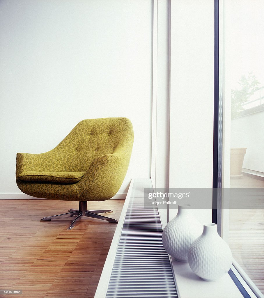 An arm chair next to a window : Stock-Foto