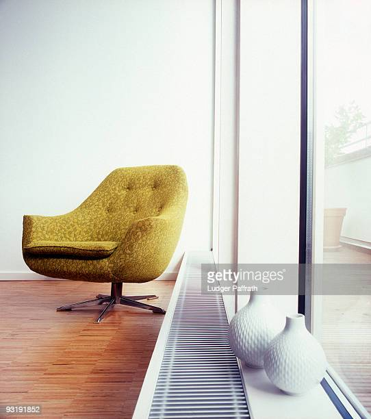 An arm chair next to a window