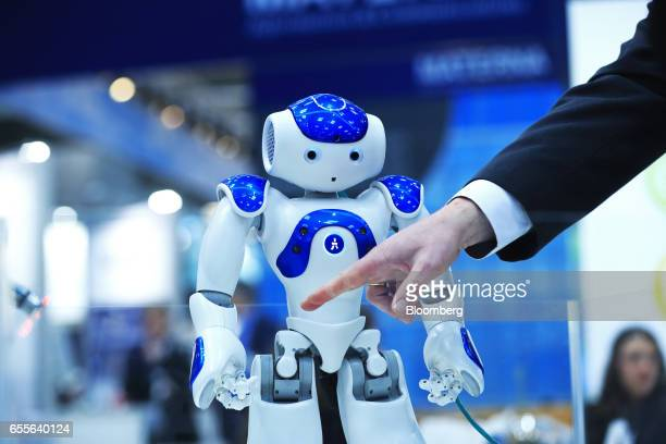 An arm gestures in front of a NAO humanoid robot developed by Softbank Corp at the CeBIT 2017 tech fair in Hannover Germany on Monday March 20 2017...
