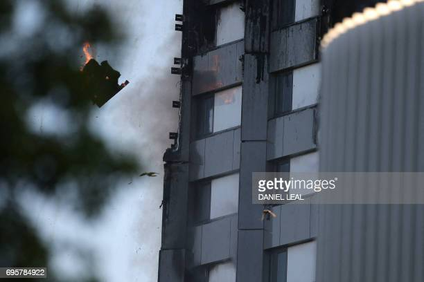 TOPSHOT An arm holding a cloth can be seen waving from a window of Grenfell Tower as a piece of burning debris falls on June 14 2017 in west London...