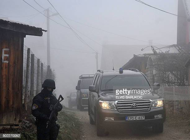 An armed Bosnian police officer stands next to police vehicles in Sarajevo's suburb of Sokolje on December 22 during search operations of permises...