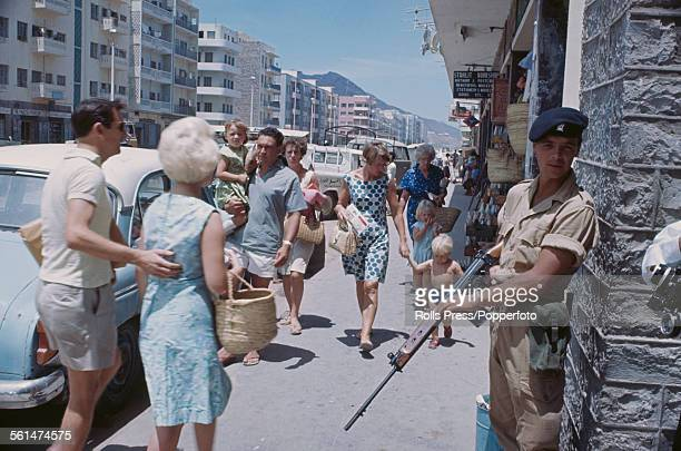 An armed British Army soldier stands guard on a shopping street in Aden during the Aden Emergency a period of unrest and insurgency in South Arabia...