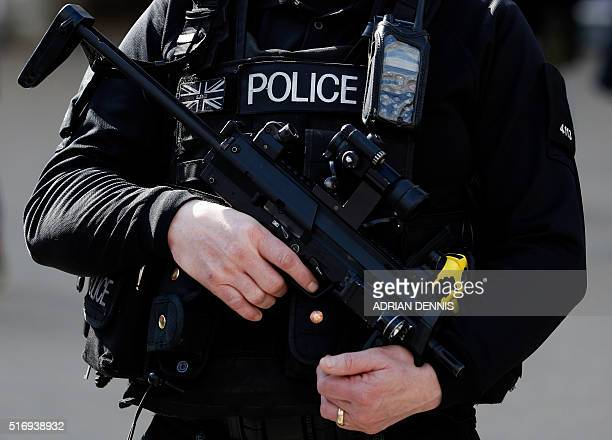 An armed British police officer holds his automatic weapon as he stands on duty in central London on March 22 2016 Britain boosted security at its...