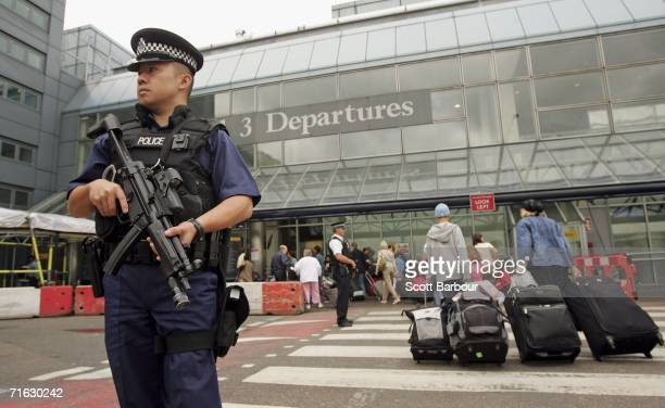 An armed British police officer patrols outside of Heathrow Airport on August 11 2006 in London England The UK security threat level is to stay at...