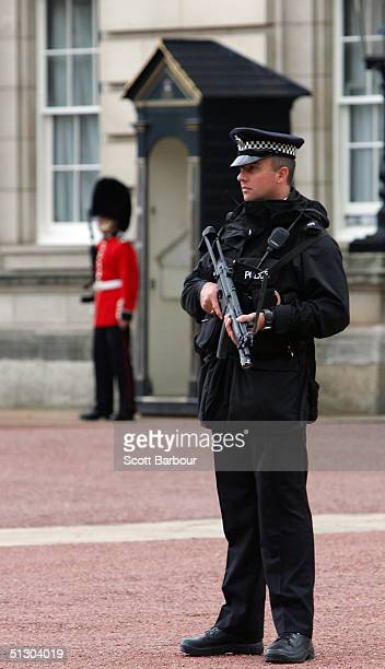 An armed British police officer stands guard near the fence which protester Jason Hatch had used a ladder to climb over the previous day on September...