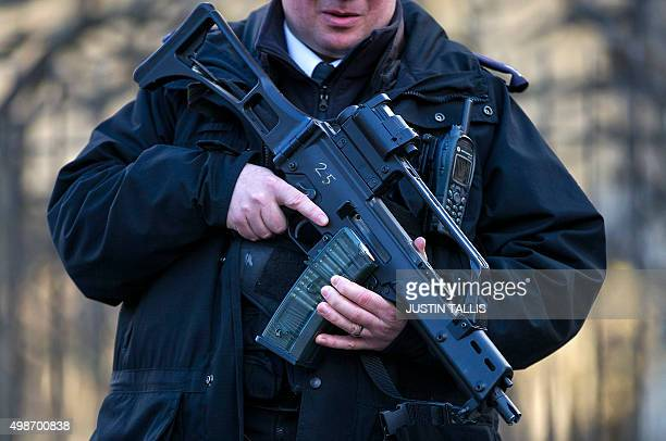An armed British police officer stands guard outside the Houses of Parliament in central London on November 25 2015 Britain announced a fresh round...
