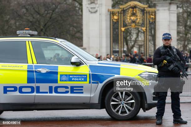 An armed British police officer stands on patrol during the Changing the Guard ceremony at Buckingham Palace in London UK on Friday March 3 2017 UK...