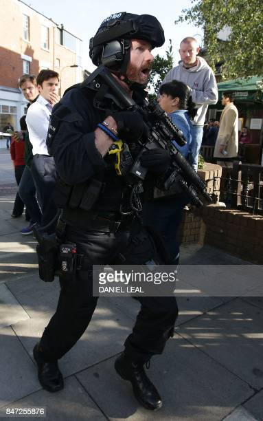 An armed British police officer works near Parsons Green underground tube station in west London on September 15 following an incident on an...