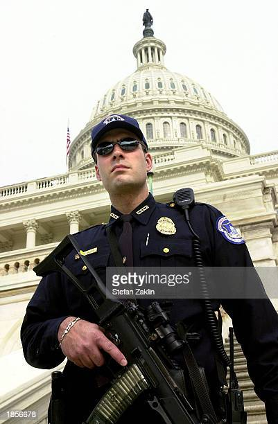 An armed Capitol policeman stands guard on the steps of the US Capitol March 18 2003 in Washington DC The Department of Homeland Security raised the...