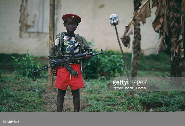 An armed child fighter with the LPC poses with a gun and red beret at a military training facility during the Liberian Civil War The Liberia Peace...