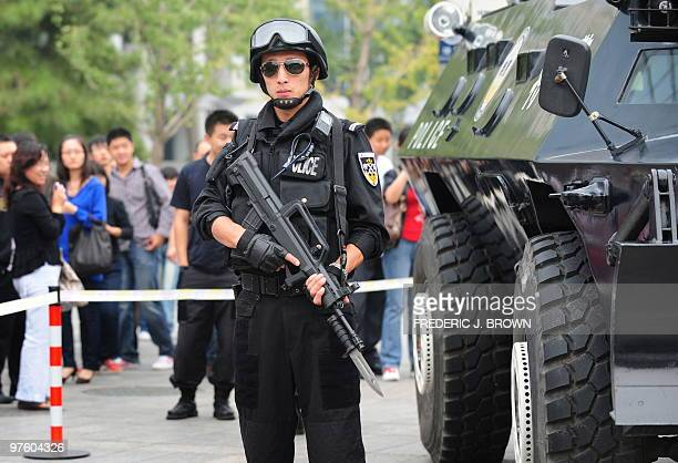 An armed Chinese special forces policeman guards an armoured personnel carrier on a street corner near Tiananmen Square as pedestrians stop to look...