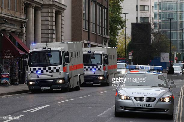 An armed City of London Police convoy escorts two prison vans as they arrive at the Old Bailey on the first day of the trial of Michael Adebolajo and...