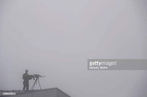 An armed Civil Guard stands on a roof of the Lavacolla airport under the fog of Santiago de Compostela on November 6 2010 as they wait for Pope...