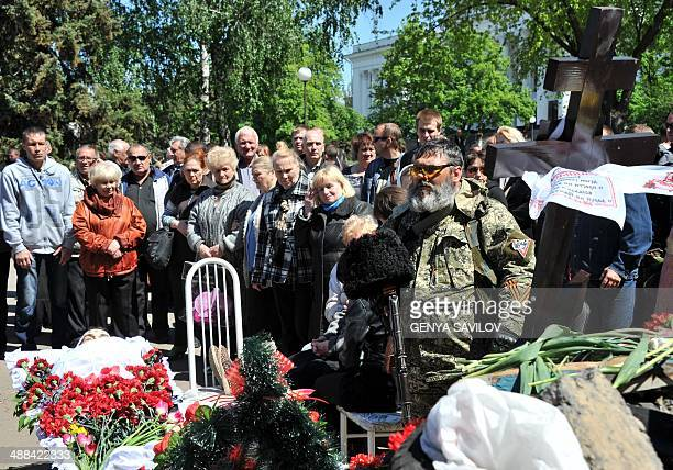 An armed Cossack attends the funeral ceremony for a proRussian activist killed during combat with Ukrainian troops in Kramatorsk eastern Ukraine on...