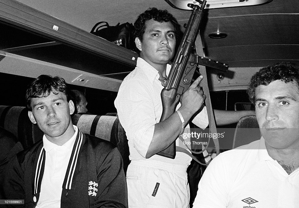 An armed escort accompanies the England team from Monterrey Airport to the Camino Real Hotel in Saltillo, Mexico during their pre-World Cup training on 25th May 1986. Pictured with the guard are team captain Bryan Robson (left) and goalkeeper Peter Shilton. (Bob Thomas/Getty Images).