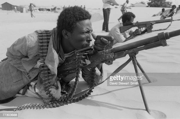 An armed fighter in Mogadishu resting his machine gun on the sand dunes during the Somalian civil war, January 1992.