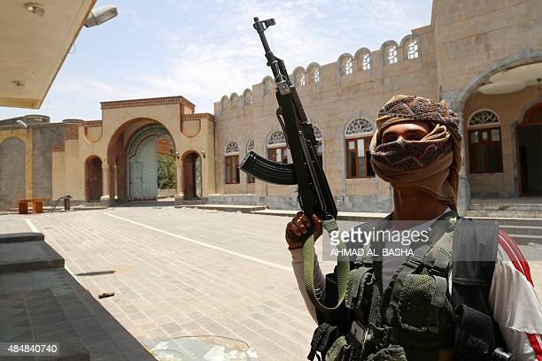 An armed fighter loyal to Yemen's exiled President Abedrabbo Mansour Hadi stands guard in the courtyard of a house of former president Ali Abdullah...
