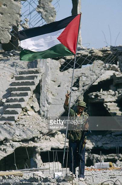An armed fighter raises his arm in victory as he stands next to a Palestinian flag near a destroyed building.