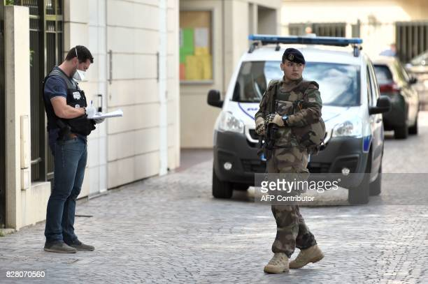 TOPSHOT An armed French soldier patrols next to a forensic police officer near the site where a car slammed into soldiers in LevalloisPerret outside...