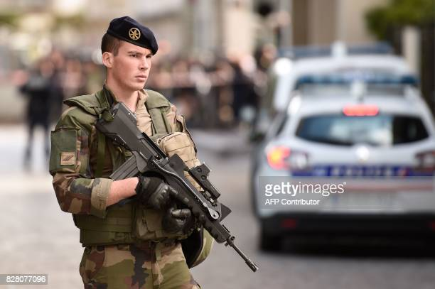 An armed French soldier stands at the site where a car slammed into soldiers in LevalloisPerret outside Paris on August 9 2017 French police launched...