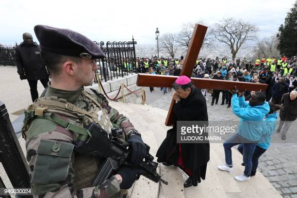 TOPSHOT An armed French soldier stands by as Archbishop of Paris Michel Aupetit carries a cross during a Stations of the Cross procession on Good...