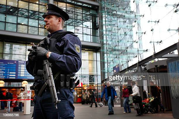 An armed german policeman secures the entrance area of the main station on November 19 2010 in Berlin Germany Germany's interior minister Thomas de...