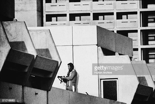 An armed German policeman stands on the roof of a dormitory where members of the Black September terrorist group had earlier captured and were...