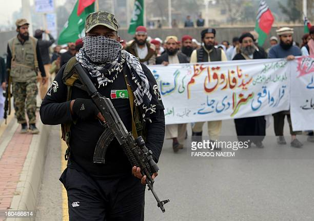 An armed guard escorts activists of Ahle Sunnat Wal Jamaat during a protest march against the killing of seminary clerics in Karachi in Islamabad on...