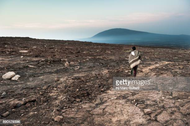 An armed guard leads tourists down the flanks of Erta Ale volcano, after viewing the lava lake. Danakil Depression, Ethiopia