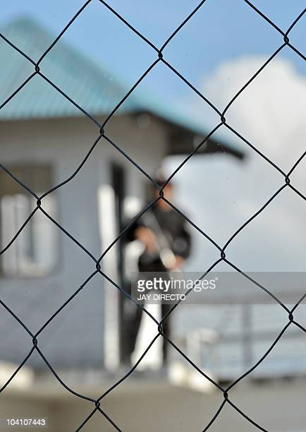 An armed guard patrols along the top of the prison walls as the trial of a political clan accused of masterminding the country's worst massacre takes...