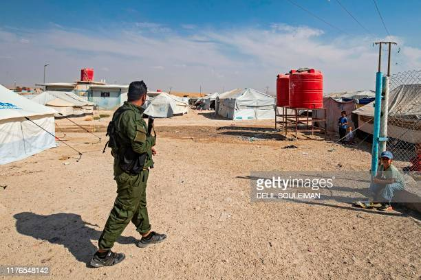 An armed guard walks among tents at the Kurdish-run al-Hol camp for the displaced where families of Islamic State foreign fighters are held, in the...