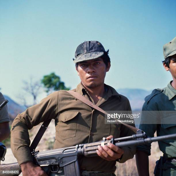 An armed guerrilla from the Fuerzas Populares de Liberation or People's Revolutionary Army stops for a picture before moving to his base below the...