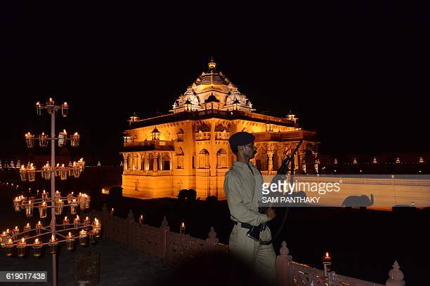 An armed Gujarat Police jawan keeps vigil as visitors throng the illuminated Akshardham Temple in Gandhinagar some 30 kms from Ahmedabad on the eve...