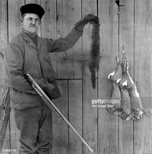 An armed hunter holds up a mink pelt while three dead rabbits hang around in the background