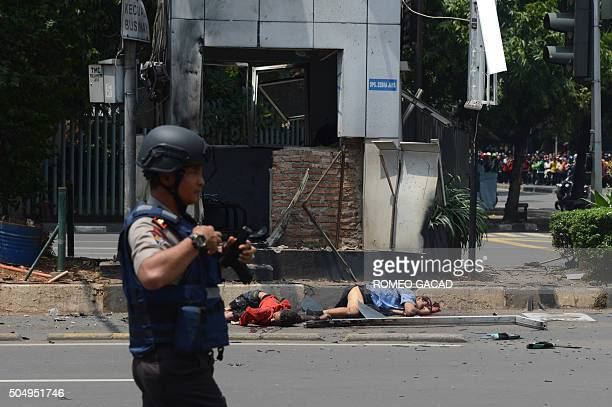 An armed Indonesian police commando walks in front of two dead bodies outside the bombdamaged traffic police outpost outside a damaged Starbucks...