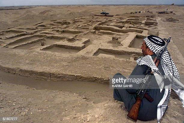 An armed Iraqi guard keeps an eye on a newlydiscovered ancient Sumerian site 13 March 2001 in Umm alAqareb 300 kilometers south of Baghdad A team of...