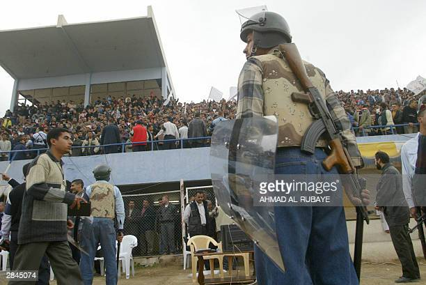 An armed Iraqi policeman in riot gear stands guard during the final between rival Baghdad clubs alZawra and alTalaba of the Baghdad Cup the first...