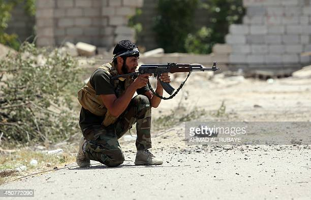 An armed Iraqi Shiite fighter from the Popular Mobilisation units supporting the Iraqi government forces guards a position during clashes with...