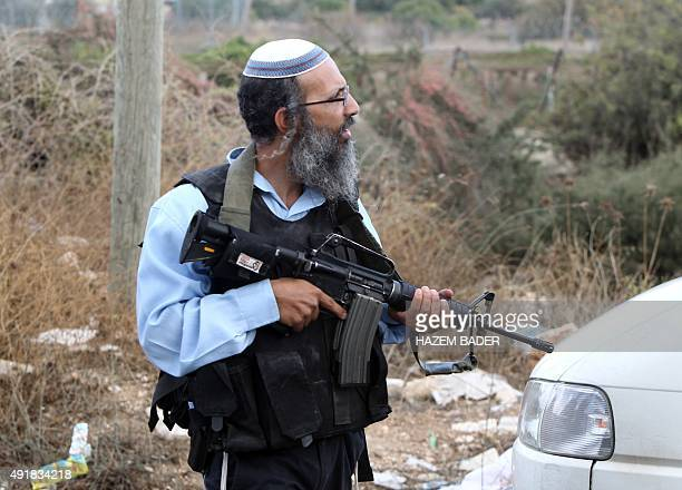 An armed Israeli settler stands guard near the Israeli settlement of Kiryat Arba near Hebron in the occupied West Bank on October 8 following a spate...