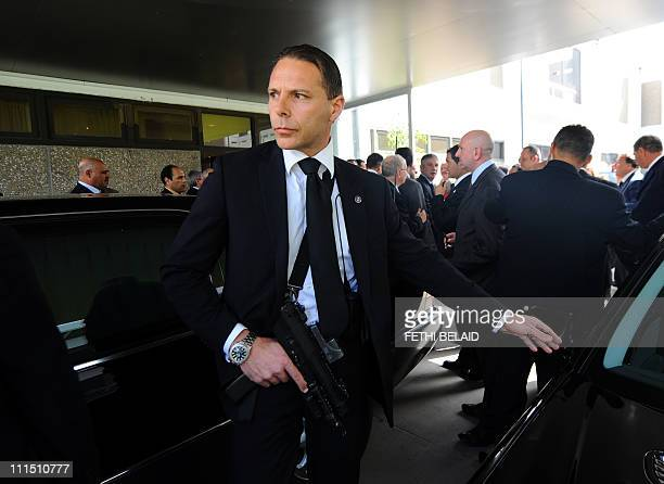 An armed Italian security guard gestures as Italian Prime Minister Silvio Berlusconi arrives on April 4 2011 at Tunis airport A new boatload of...