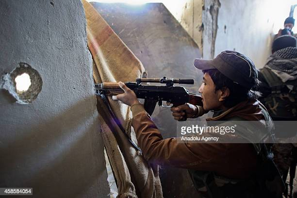 An armed Kurdish fighter boy is seen during the clashes with Islamic State of Iraq and Levant members in Kobani Syria on November 7 2014 ISIL have...