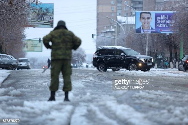 An armed man in military fatigues blocks access to the government buildings in eastern Ukraine's rebelheld Lugansk on November 22 2017 The patrols...
