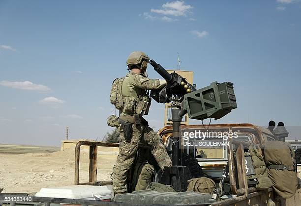 An armed man in uniform identified by Syrian Democratic forces as a member of US special operations forces stands in the back of a pickup truck in...