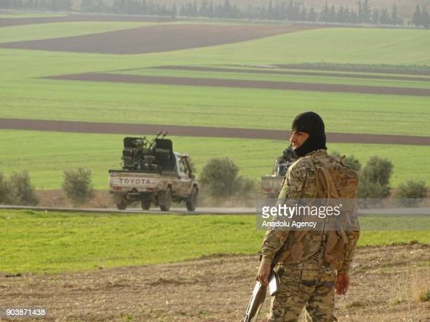 An armed man is seen behind a truck with a weapon loaded on its back in Idlib Syria on January 11 2018 Assad Regime and its supporter terrorist...